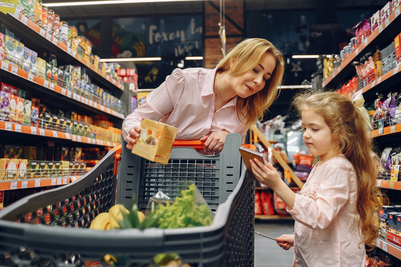 Mother and daughter shopping in grocery store for favorite brands.